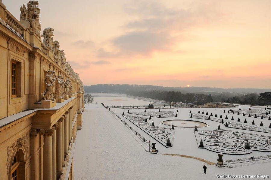 Coucher de soleil sur le château de Versailles enneigé