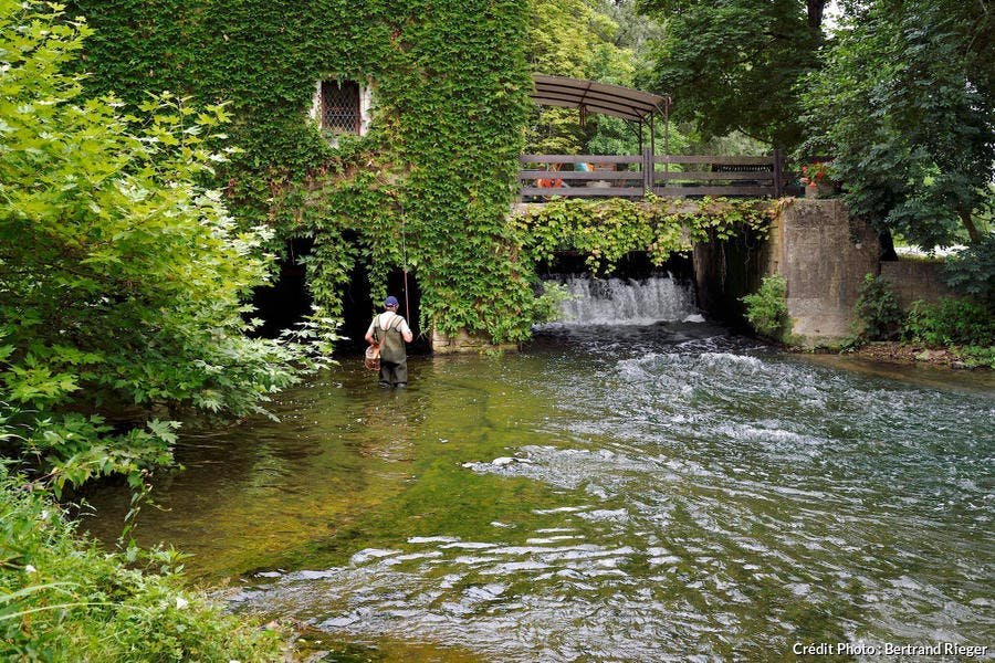 Pêcheur à la ligne au pied du moulin de Taillepetit, dans le Périgord Blanc (Dordogne)