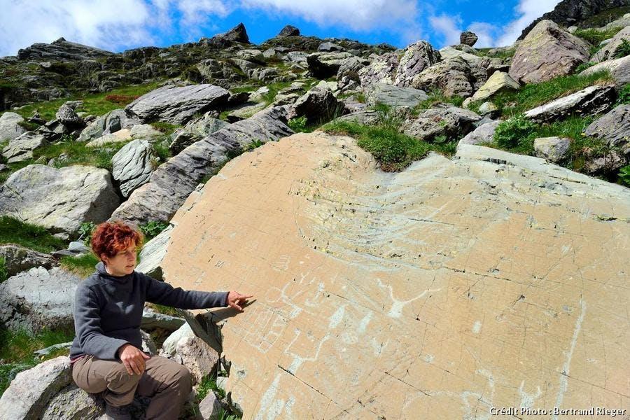 Archéologue Nicoletta Bianchi devant la roche de l'Éclat, gravée de figures corniformes et de poignards