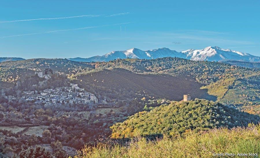 Castelnou, avec au loin, le massif du Canigou avec son pic à 2 784m