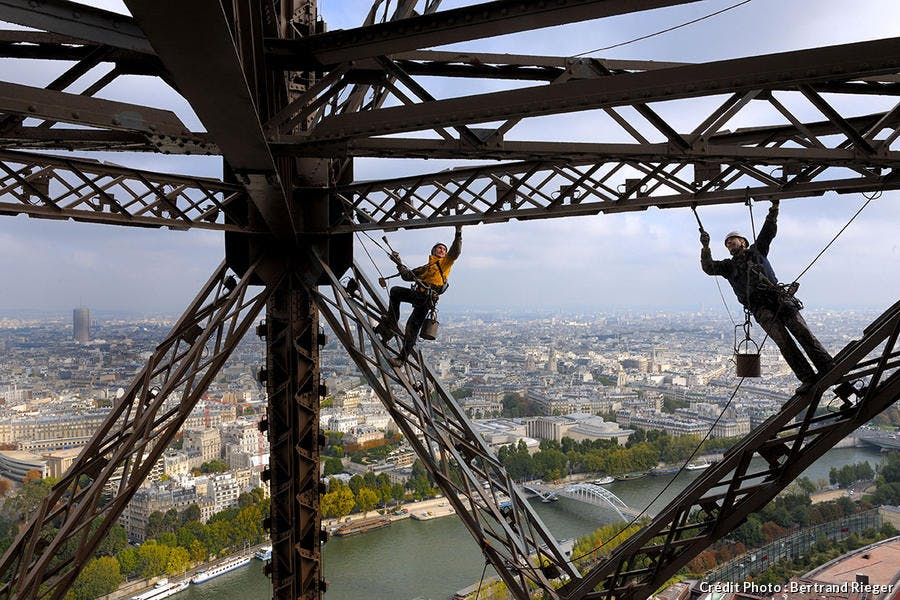 Vue imprenable sur Paris pour un peintre qui travaille sur la tour Eiffel